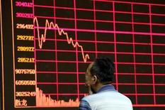 Un inversor mira un tablero electrónico que muestra información bursátil, en la Bolsa de Shanghái, en Pekín. 26 de agosto de 2015. Las acciones chinas bajaron el viernes antes de una serie de datos económicos, luego de que algunos inversores recogieron ganancias de un rebote de un mes que refleja las expectativas de un primer trimestre sólido. REUTERS/Jason Lee