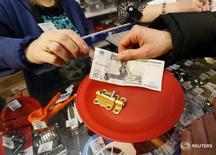 Покупатель расплачивается в магазине в Красноярске 21 января 2016 года. Индекс потребительской уверенности, отражающий совокупные потребительские ожидания населения, в первом квартале 2016 года снизился по сравнению с четвертым кварталом 2015 года на 4 процентных пункта до минус 30 процентов, сообщил Росстат в пятницу. REUTERS/Ilya Naymushin