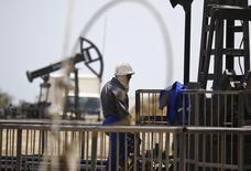 Рабочий на нефтяном месторождении в Баку. 16 июня 2015 года. Министр энергетики Азербайджана Натиг Алиев собирается посетить встречу ведущих стран-экспортеров нефти, которая состоится в Дохе 17 апреля, сообщило Минэнерго Азербайджана в понедельник. REUTERS/Kai Pfaffenbach