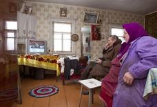 Пожилая пара смотрит по телевизору выступление президента Белоруссии Александра Лукашенко в белорусской деревне Ракшин. 6 декабря 2010 года. Белоруссия, теряющая бюджетные доходы из-за снижения экономики на фоне падения спроса в России, повышает на три года пенсионный возраст для мужчин и женщин, говорится в указе президента страны Александра Лукашенко. REUTERS/Vasily Fedosenko