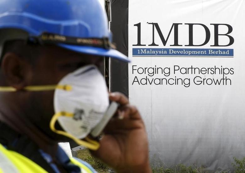 A construction worker talks on the phone in front of a 1Malaysia Development Berhad (1MDB) billboard at the Tun Razak Exchange development in Kuala Lumpur, Malaysia, February 3, 2016. REUTERS/Olivia Harris