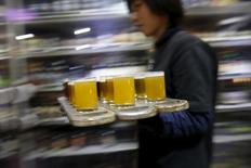 A bartender carries glasses of craft beer to customers at a microbrewery NBeer Pub in Beijing, China, March 6, 2016. Picture taken March 6, 2016. REUTERS/Kim Kyung-Hoon