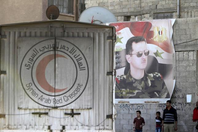 An aid convoy of the Syrian Arab Red Crescent enters the Wafideen Camp, controlled by Syrian government forces, near a poster of Syria's president Bashar al-Assad, to deliver aid into the rebel-held besieged Douma neighborhood of Damascus, March 4, 2016. REUTERS/Omar Sanadiki