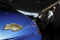 Peatones pasan junto a un vehículo de Chevrolet, en una concesionaria en Santiago. 1 de junio de 2009. La venta de vehículos livianos y medianos en Chile creció un 10,2 por ciento interanual en el primer trimestre, apoyada en la apreciación de la moneda local y pese al bajo dinamismo de la demanda interna, dijo el lunes un informe del gremio del sector. REUTERS/Ivan Alvarado