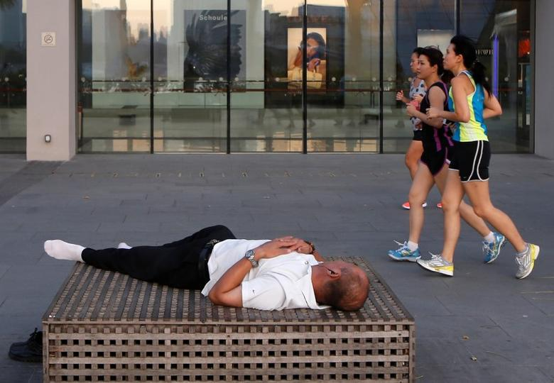 A man sleeps outside a mall as people jog past in Singapore March 6, 2014. REUTERS/Edgar Su