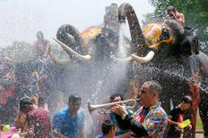 A man plays a trumpet while people are splashed by elephants with water during the celebration of the Songkran water festival in Thailand's Ayutthaya province, north of Bangkok. REUTERS/Jorge Silva