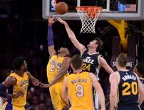 Apr 13, 2016; Los Angeles, CA, USA; Los Angeles Lakers forward Kobe Bryant (24) puts up a reverse layup past Utah Jazz center Jeff Withey (24) during the first quarter at Staples Center. Kobe Bryant played in his final game and is retiring.  Robert Hanashiro-USA TODAY Sports