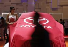 A model stands beside a veiled, new Toyota Sienta car at the Indonesian International Motor Show in Jakarta, Indonesia, April 7, 2016. REUTERS/Beawiharta