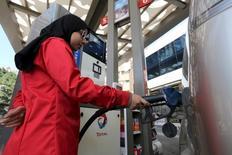 Una empleada rellena el estanque de un auto en una gasolinera en El Cairo, Egipto. 24 de febrero de 2016. Las exportaciones de petróleo saudíes retrocedieron en febrero a 7,553 millones de barriles por día (bpd), desde 7,835 millones de bpd en enero, mostraron datos oficiales el lunes. REUTERS/Mohamed Abd El Ghany