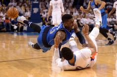 Apr 18, 2016; Oklahoma City, OK, USA; Dallas Mavericks guard Wesley Matthews (23) and Oklahoma City Thunder guard Russell Westbrook (0) collide while diving for a loose ball during the third quarter in game two of the first round of the NBA Playoffs at Chesapeake Energy Arena. Mark D. Smith-USA TODAY Sports