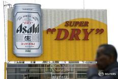 Мужчина проходит мимо рекламы Asahi Breweries, Ltd. в Токио 1 декабря 2008 года.  Пивоваренная компания Anheuser-Busch InBev, которая находится в процессе приобретения конкурирующего SABMiller, сообщила, что принимает предложение японской Asahi Group о покупке Peroni и некоторых других брендов SAB. REUTERS/Stringer