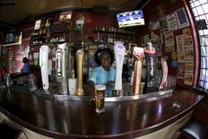 Бармен подает стакан пива Castle Lager компании SABMiller в Кейптауне 10 ноября 2015 года. Пивоваренный гигант SABMiller продал на 4 процента больше лагера в четвертом квартале по сравнению с аналогичным периодом прошлого года, что может свидетельствовать об улучшении ситуации в компании во второй половине финансового года. REUTERS/Mike Hutchings