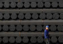 A worker walks past a pile of steel pipe products at the yard of Youfa steel pipe plant in Tangshan in China's Hebei Province November 3, 2015.   REUTERS/Kim Kyung-Hoon/File Photo