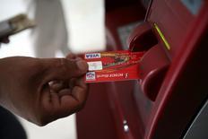Visa Inc, la mayor red de procesamiento de pagos del mundo, bajó el jueves su previsión de crecimiento de ingresos para todo el año, lo que provocaba una baja de sus acciones de un 4,4 por ciento a 77,25 dólares en las operaciones tras el cierre del mercado regular.  En la imagen de archivo, un cliente usa su tarjeta para sacar dinero de un cajero automático en Jammu el 14 de octubre de 2008. REUTERS/Amit Gupta