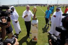 FIFA's newly elected president Gianni Infantino poses with the Qatar Workers Cup trophy in Doha, Qatar, April 22, 2016. REUTERS/Naseem Zeitoon