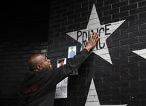 Donnie Straub of Minneapolis touches a star bearing U.S. music superstar Prince's name on an exterior wall of First Avenue, the nightclub where Prince got his start in Minneapolis, Minnesota, April 21, 2016. REUTERS/Craig Lassig