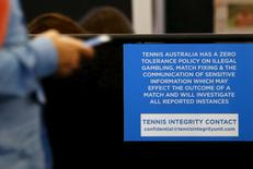 A man uses his phone next to a sign displaying the contact for the Tennis Integrity Unit at the Australian Open tennis tournament at Melbourne Park, Australia, January 21, 2016. REUTERS/Brandon Malone