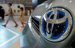 Visitantes caminan frente aun vehículo híbrido modelo Prius de Toyota Motor Corp en la sala de exhibición de la compañía en Tokio. 5 de agosto, 2014. La automotriz japonesa Toyota Motor Corp planea vender automóviles híbridos que se conecten a tomas de electricidad en China a partir del 2018, dijo el domingo el jefe de operaciones en el país, Hiroji Onishi. REUTERS/Yuya Shino