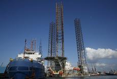Нефтяная вышка среди кораблей у острова Батам, Индонезия. Цены на нефть упали более чем на 1 процент в ходе торгов понедельника, поскольку трейдеры фиксировали прибыль после трёх недель роста нефтяных котировок, негативно влияет на цены и скачок курса доллара в конце прошлой недели. REUTERS/Edgar Su