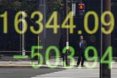 Un hombre reflejado en una pantalla electrónica que muestra el índice Nikkei en el exterior una correduría en Tokio, Japón, 18 de abril de 2016. Las acciones japonesas cayeron el lunes luego de que los inversores recogieron ganancias de un repunte de cuatro días, en medio de las expectativas de una mayor relajación de la política monetaria del Banco de Japón. REUTERS/Toru Hanai