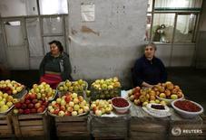Женщины продают фрукты на рынке в Ереване 31 октября 2009 года. Центральный банк Армении рассчитывает подстегнуть совокупный спрос и вернуть инфляцию к целевым 4 процентам плюс-минус 1,5 процентного пункта за счет снижения ключевой процентной ставки, траектория которой в текущем году будет зависеть от динамики потребительских цен. REUTERS/David Mdzinarishvili