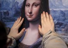 Visitante do Museu do Prado, em Madri, toca obra Mona Lisa. 13/2/2015.  REUTERS/Andrea Comas