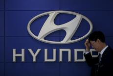 Продавец автомобилей стоит рядом с логотипом Hyundai Motor в магазине компании в Сеуле. Южнокорейская Hyundai Motor отчиталась о падении прибыли девятый квартал подряд из-за ухудшения спроса на внедорожники в Китае, крупнейшем для компании рынке. EUTERS/Kim Hong-Ji