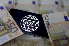 """Логотип системы SWIFT на фоне купюр валюты евро в Зенице 26 января 2016 года. SWIFT, глобальная финансовая сеть, используемая банками для перевода миллиардов долларов ежедневно, предупредила клиентов в понедельник об обнаружении """"ряда недавних киберинцидентов"""", в рамках которых хакеры пересылали вредоносные сообщения через систему. REUTERS/Dado Ruvic/File Photo"""