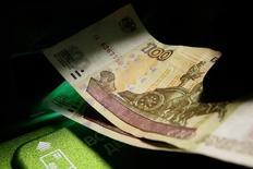 Клиент вносит деньги в банкомат. Рубль торгуется в минусе днем среды, невзирая на новые многомесячные максимумы нефти, поскольку есть опасения ужесточения риторики ФРС, а также на рынке присутствует отмечаемый дилерами  спрос на подешевевшую валюту при сокращении продаж экспортной выручки после пика налогов. REUTERS/Ilya Naymushin