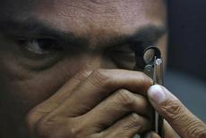 Проверяющий изучает качество огранки полированного алмаза в индийском Сурате 5 января 2013 года. Индия заметила рост спроса на бриллианты в США. REUTERS/Amit Dave