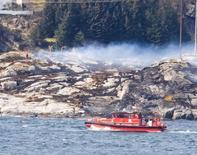Команда спасателей реботает на месте крушения вертолета в Норвегии. Вертолет с 13 людьми на борту разбился у западного побережья Норвегии в пятницу, и выживших найти пока не удалось, сообщил источник в спасательных службах страны.    NTB Scanpix/Bergens Tidende/via REUTERS