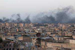 Smoke rises after airstrikes on the rebel-held al-Sakhour neighborhood of...