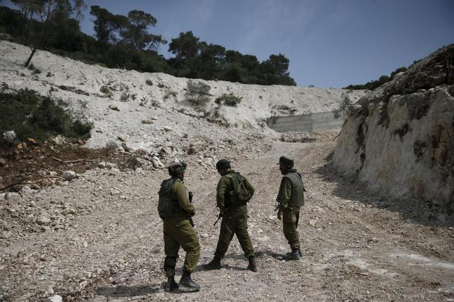 Israeli soldiers observe the area where the Israeli army is excavating part of a cliff to create an additional barrier along its border with Lebanon, near the community of Shlomi in northern Israel April 6, 2016. REUTERS/Ronen Zvulun