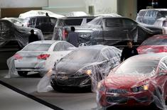 Vehicles are covered with protective wrap as workers prepare the General Motors automakers display ahead of the media preview of the North American International Auto Show at Cobo Center in Detroit, Michigan January 11, 2014.  REUTERS/Rebecca Cook/File Photo