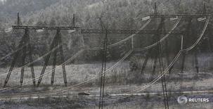 Машина проезжает мимо опор ЛЭП к югу от Красноярска 24 октября 2015 года. Правительство РФ вернуло возможность продажи 100 процентов мощности сибирских гидроэлектростанций по свободным ценам с 1 мая текущего года, на восемь месяцев раньше, чем планировало. REUTERS/Ilya Naymushin