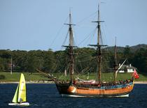 A small sailing boat sails past the replica of the famous 18th century ship The Endeavour as it sits anchored in Botany Bay, Australia April 17, 2005.  REUTERS/David Gray/File Photo
