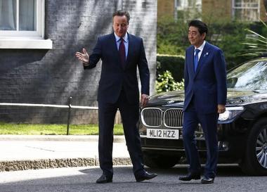 Britain's Prime Minister David Cameron greets his Japanese counterpart...