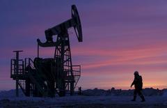 Foto de archivo de un trabajador caminando cerca de una unidad de bombeo de petróleo, propiedad de Bashneft, en Bashkortostan, Rusia. 28 de enero de 2015. Las negociaciones entre importantes productores de crudo sobre posibles límites a la producción, con el objetivo de elevar los débiles precios del petróleo, deberían reiniciarse desde el comienzo, dijo el viernes un portavoz del Kremlin. REUTERS/Sergei Karpukhin