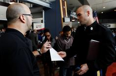 David Wallace (L) of Lockheed Martin interviews an applicant at a job fair for veterans and their spouses held by the U.S. Chamber of Commerce and the Washington Nationals baseball club at Nationals Park in Washington December 5, 2012.   REUTERS/Gary Cameron
