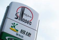A Sinopec logo is seen on top of a logo of Easy Joy store at a gas station in Beijing, September 16, 2011. REUTERS/Sean Yong