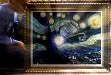 """Мужчина готовит картину Винсента Ван Гога """"Звёздная ночь"""" к выставке в Риме 17 января 2001 года. Тайваньская компания с помощью четырёх миллионов разноцветных пластиковых бутылок создала гигантскую копию картины Винсента Ван Гога """"Звёздная ночь"""", чтобы привлечь внимание людей к проблеме переработки отходов. Alessia Pierdomenico / Reuters"""