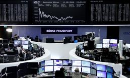 Traders work at their desks in front of the German share price index, DAX board, at the stock exchange in Frankfurt, Germany, May 11, 2016.     REUTERS/Staff/Remote