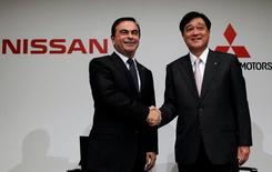 Глава Nissan Motor Карлос Гон и президент Mitsubishi Motors Corp. Осаму Масуко обмениваются рукопожатием на пресс-конференции в Токио. Компания Nissan Motor Co согласилась приобрести 34 процента акций Mitsubishi Motors Corp, рассчитывая посредством сделки стоимостью в $2,2 миллиарда фактически получить контроль над своим менее крупным конкурентом, оказавшимся в центре скандала с фальсификацией данных о расходе топлива в технической документации.  REUTERS/Toru Hanai/File Photo