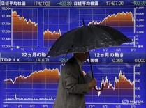 Мужчина проходит мимо экрана с графиком изменения индекса Nikkei в Токио 8 сентября 2015 года. Японские акции завершили волатильные торги пятницы в минусе в связи с фиксацией прибыли и беспокойствами о влиянии сильной иены на прибыль компаний. REUTERS/Issei Kato