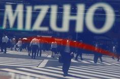 Логотип Mizuho Financial Group на отделении  компании в Токио. Японская банковская группа Mizuho Financial Group Inc в пятницу отчиталась о росте прибыли на 9,6 процента за последний финансовый год, превзойдя ожидания аналитиков, благодаря доходам от продажи акций, которые позволили нивелировать слабость её ключевого кредитного бизнеса. REUTERS/Yuriko Nakao/File Photo