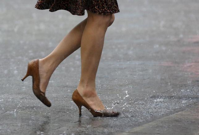 A woman walks in heavy rain caused by typhoon Etau in Tokyo's business district September 9, 2015. REUTERS/Toru Hanai/File photo