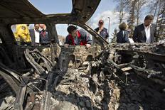 Canadian Prime Minister Justin Trudeau looks into a burnt out car while visiting neighborhoods devastated by the wildfire that forced the evacuation of the city in Fort McMurray, Alberta, Canada May 13, 2016. REUTERS/Jason Franson/Pool