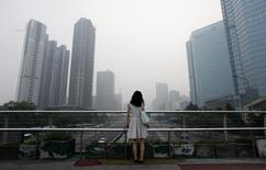 """A woman stands on an overhead bridge near the construction site of  """"Kaisa Plaza"""", then named """"Changan No. 8"""" (L), on a hazy day in Beijing's central business district in this July 28, 2012 file picture. REUTERS/Jason Lee/Files"""