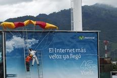 Imagen de archivo de un trabajador colocando un maniquí con un paracaídas en un cartel publicitario de Movistar que presenta la banda ancha 4G, en San José. Chile completó el demorado despliegue de la red de telefonía de cuarta generación (4G), con la puesta en marcha para uso comercial de una banda de frecuencia que mejorará la conectividad y transferencia de datos en uno de los países con más penetración de internet en la región. REUTERS/Juan Carlos Ulate