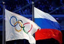 """Российский и олимпийский флаги на церемонии закрытия Олимпийских игр в Сочи. 23 февраля 2014 года. Обвинения в употреблении допинга российскими спортсменами во время сочинской Олимпиады, если они подтвердятся, переведут проблему в новую шокирующую плоскость и станут свидетельством """"беспрецедентного уровня криминала"""", сказал в среду президент Международного олимпийского комитета (МОК) Томас Бах. REUTERS/Jim Young/File Photo"""